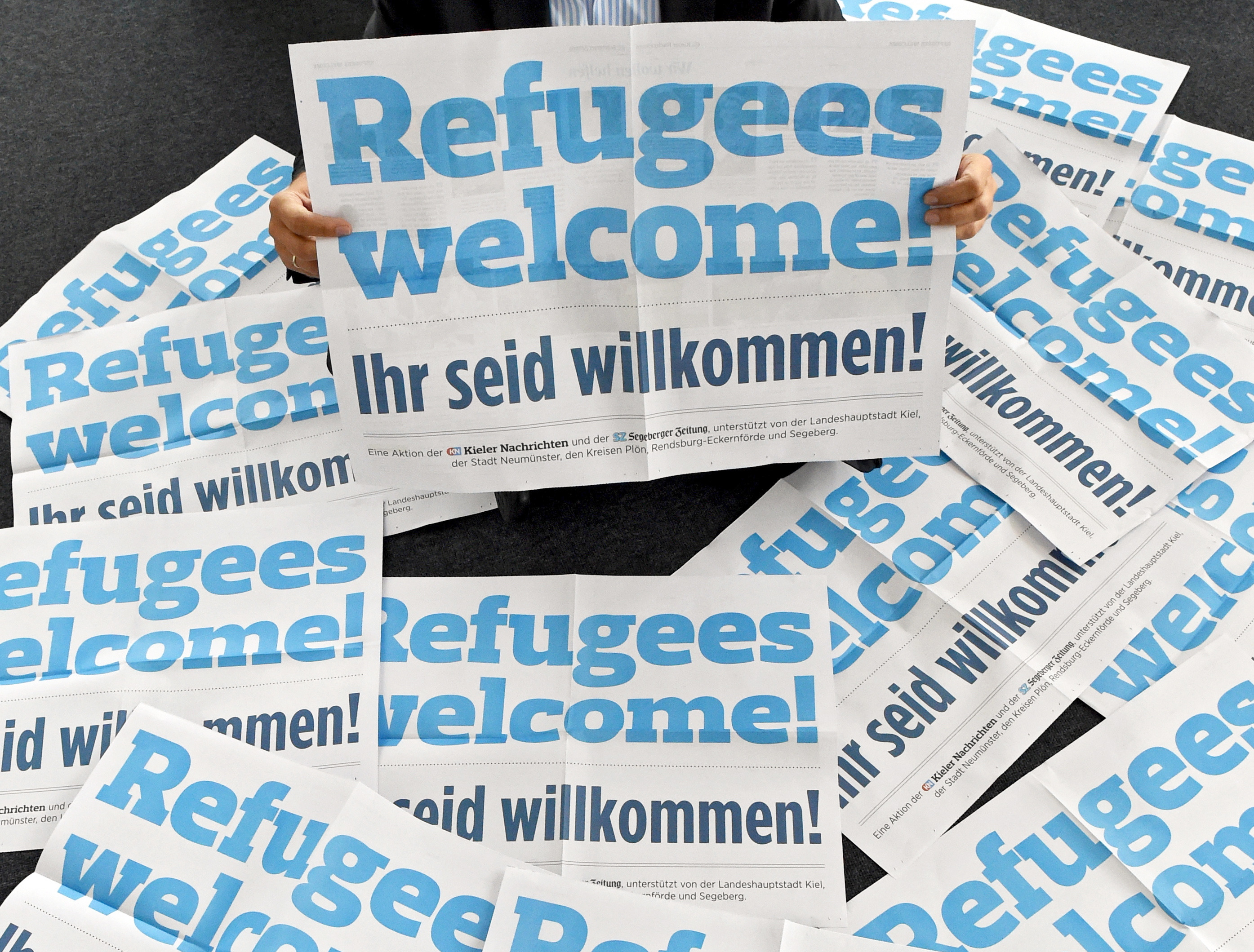 Christian Longardt, Editor in Chief of the 'Kieler Nachrichten' newspaper, sits amid posters which read 'Refugees Welcome - you are welcome' in Kiel, northern Germany, 04 September 2015. The newspaper printed 350,000 copies of the poster and plans to distribute them as a newspaper supplement in Schleswig-Holstein.