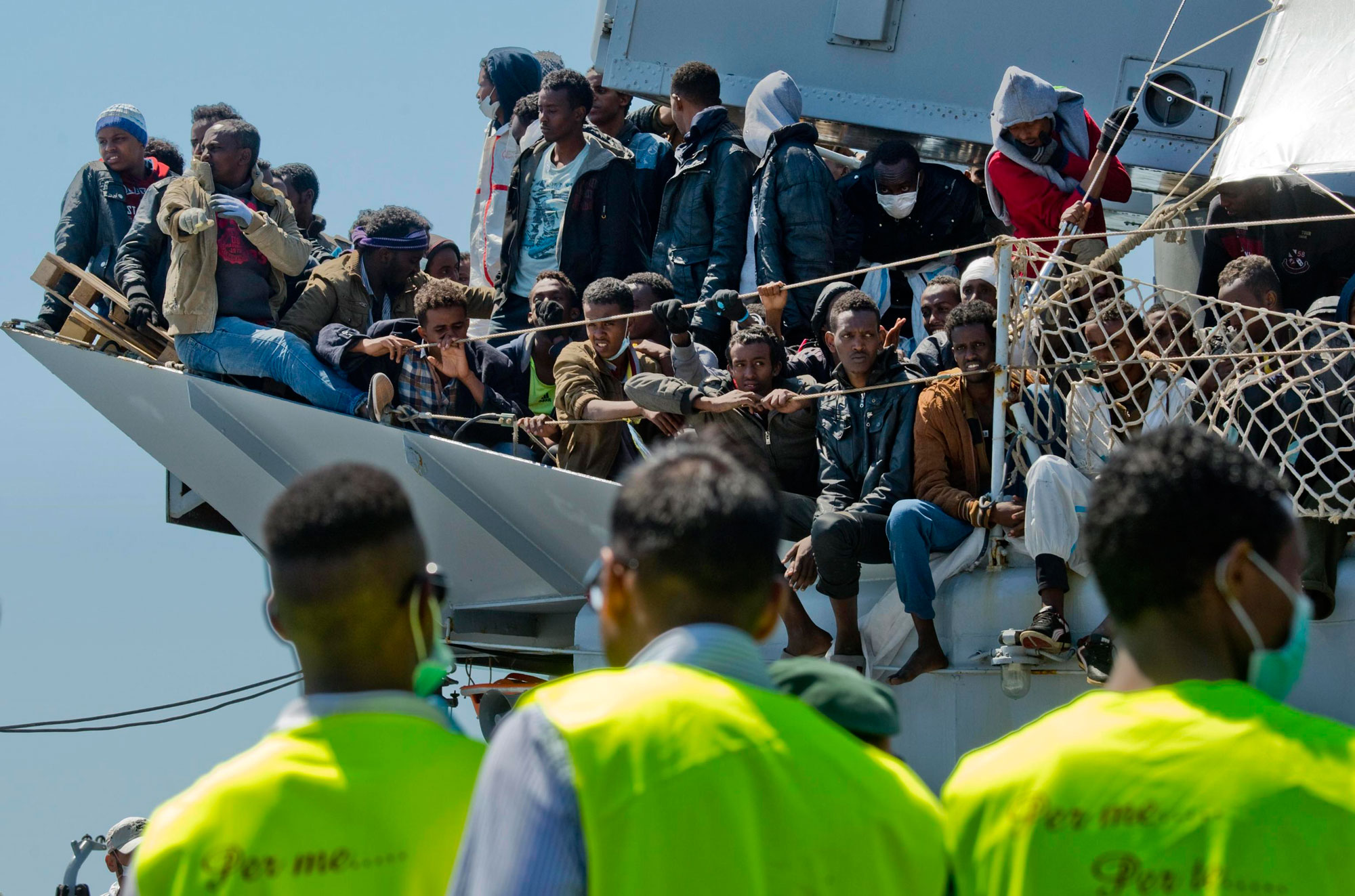 Some of a group of 545 migrants sit on the deck of the Italian navy 'Chimera' vessel while rescue workers gather in front of it as the vessel arrives in Salerno, Italy, 22 April 2015. Of these migrants, about fifty will remain in Campania region, the others will be transferred in Piemonte, Lombardia, Liguria, Veneto, Emilia Romagna, Lazio and Calabria regions. More than 600 would-be asylum seekers reached Italy's shores early 22 April, days after a deadly Mediterranean shipwreck, while top officials from the European Union and African Union were due to discuss migration at talks in Brussels. The Italian navy wrote on Twitter that 446 migrants who were rescued Tuesday some 150 kilometers south-east of the coast of the southern region of Calabria were disembarked in Augusta, Sicily. A further 112 migrants, picked up by the coast guard late on Tuesday from a sinking dinghy at about 90 kilometers north-east of Tripoli, reached the island of Lampedusa, Italy's southern outpost.