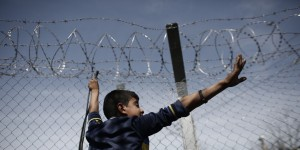 epa05248134 A refugee child gesture to other refugees as he stands in front of  barbed wire fence during a protest demanding the opening of the borders at the border line between Greece and FYROM at the refugee camp of Idomeni, Greece, 07 April 2016. Migrants who refuse to apply for asylum are to be deported to Turkey, in accordance with a tit-for-tat agreement between the European Union (EU) and Turkey on the refugee and migration crisis.  EPA/KOSTAS TSIRONIS