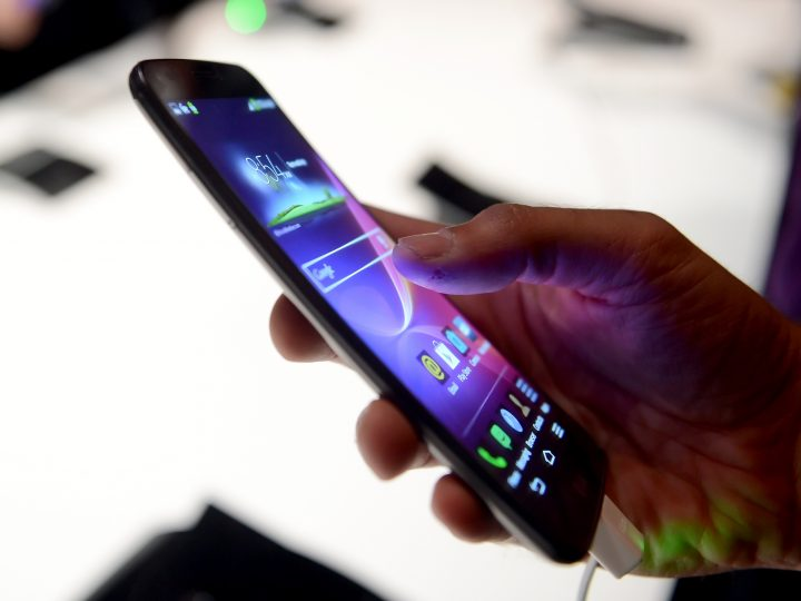 epa04010521 A journalist tries out the new LG G Flex Android Smartphone featuring a curved, flexible body and screen during a media presentation at the consumer electronics show CES in Las Vegas, USA, 06 January 2014. CES, the world's largest annual consumer technology trade show runs from 07 to 10 January 2014 and is expected to feature 3,200 exhibitors showing off their latest products and services to about 150,000 attendees.  EPA/BRITTA PEDERSEN