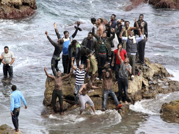 epa05273462 Some Sub-Saharan migrants celebrate after entering the Spanish enclave of Ceuta in Africa, 23 April 2016. Some 90 migrants illegally entered Ceuta after skirting the breakwater of Benzu frontier, as Moroccan forces stopped another group of migrants.  EPA/REDUAN