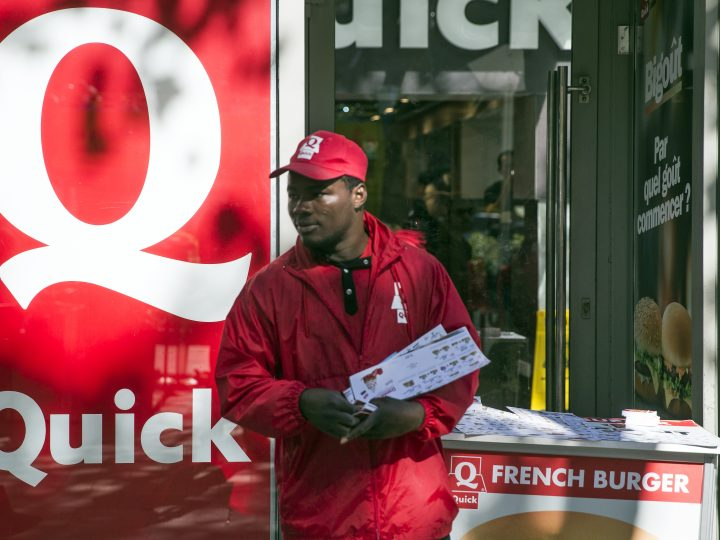 epa04954225 A 'Quick' employee distributes promotional flyers in front of the fast-food restaurant on the Champs Elysees in Paris, France, 28 September 2015. Burger King, US the burger giant, announced on Monday that it is in negotiations to take over the 509 outlets run in France by Belgian chain Quick.  EPA/ETIENNE LAURENT