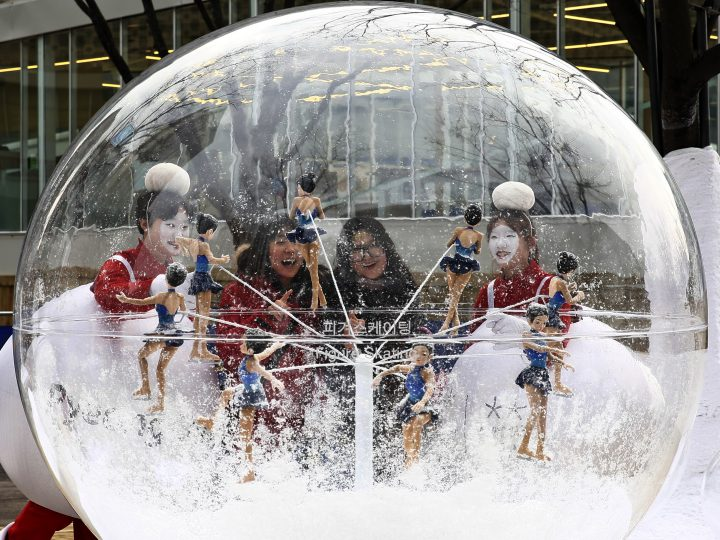 epa05077545 Two young women are flanked by South Korean dancers as they admire the figure skating sculptures for 2018 Pyeongchang Olympics in giant transparent shere during a publicity event  in front of the Seoul City Hall in Seoul, South Korea, 21 December 2015.  The first Winter Olympic Games held in South Korea will kick off on 09 February 2018.  EPA/JEON HEON-KYUN