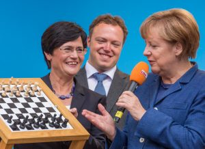 epa04398341 Premier of Thuringia Christine Lieberknecht (L) gives a chess board to German Chancellor Angela Merkel (R) during an election campaign event of the German Christian Democratic Union Party (CDU) in Apolda, Germany, 13 September 2014. At (C) is CDU Thuringia Secretary General Mario Vogt. Thuringia will hold parliamentary elections on 14 September.  EPA/MICHAEL REICHEL