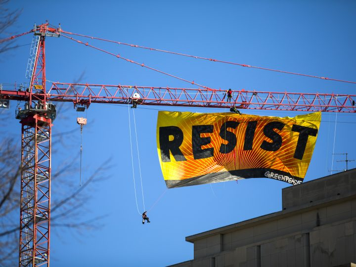 epa05749789 Seven Greenpeace activists unfurl a 70-foot by 35-foot banner reading the word 'Resist' from a tower crane near the White House in Washington, DC, USA, 25 January 2017. The activists are calling for those who want to resist Trump's attacks on environmental, social, economic, and educational justice to contribute to a better America.  EPA/JIM LO SCALZO
