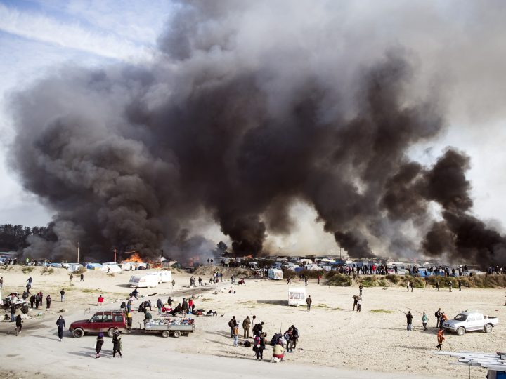epa05620910 YEARENDER 2016 OCTOBER  Smoke billows from a fire after tents and shacks were set ablaze in the makeshift camp the 'Jungle' during its evacuation in Calais, France, 26 October 2016. The operation to dismantle the 'Jungle' migrant camp in the French port city of Calais continued into a third day. French authorities estimate that there were some 6,000 migrants living in the camp at the beginning of the week, while humanitarian organizations put the number at 8,000. Over 4,000 people have so far been bussed out of the camp to 450 reception centers across the country, according to the French Interior Ministry.  EPA/ETIENNE LAURENT