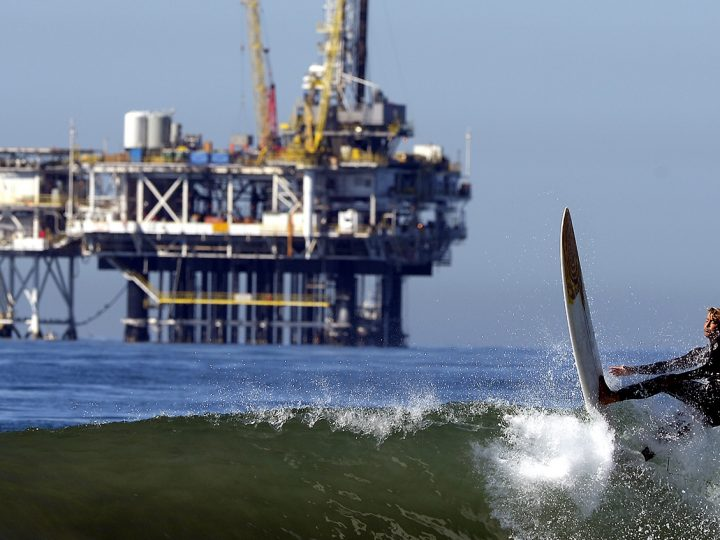 epa03889319 A surfer rides a wave with an oil drilling rig in the background in Huntington Beach, California, USA 29 September 2013.  Along southern California coast from Santa Barbara to Huntington Beach are a number of oil rigs in a petroleum rich region.  EPA/MICHAEL NELSON