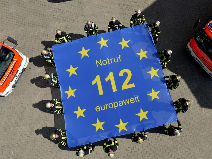 epa05436113 A picture made available on 22 July 2016 shows emergency personnel from the Fire Station 1 holding up a flag with the inscription 'Notruf 112 europaweit' (lt. Emergency call 112 Europe-wide) in Stuttgart, Germany, 18 July 2016. The European emergency service 112 celebrates its 25th anniversary on 29 July 2016.  EPA/FRANZISKA KRAUFMANN