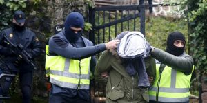 epa05721769 Two masked policemen escort an alleged Moroccan jihadist (C) from a house after he was arrested in San Sebastian, Basque Country, northern Spain, 16 January 2016. The defendant is accused of recruiting people to commit terrorist attacks in Europe.  EPA/JUAN HERRERO