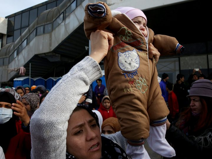 epa05774909 An Afghan migrant woman holds her baby aloft during a protest in the former airport of Athens that is used as a refugee camp, in Athens, Greece, 06 February 2017. The refugees blocked the entrance of the camp and prevented Migration Minister Yannis Mouzalas from entering the premises, to draw attention to poor living conditions at the camp.  EPA/ORESTIS PANAGIOTOU