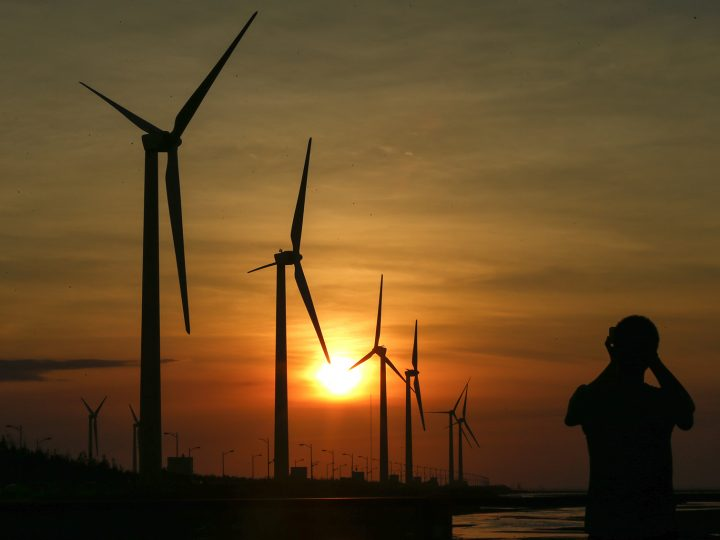 epaselect epa05378797 A picture made available on 20 June 2016 shows a silhouette of a man in front of wind turbines in Taichung, Taiwan, 19 June 2016. As of 2016 there are 326 wind turbines operating in Taiwan. The first hydropower plant opened in Taiwan in June 1995. Taiwan's Photovoltaic power generation project was divided into two stages, the first stage was completed in December 2011 and the second stage in December 2014. By the year 2020 the legislature of Taiwan plans to increase its solar energy output to 4,500 Megawatt, as public demands for green energy sources rise.  EPA/RITCHIE B. TONGO