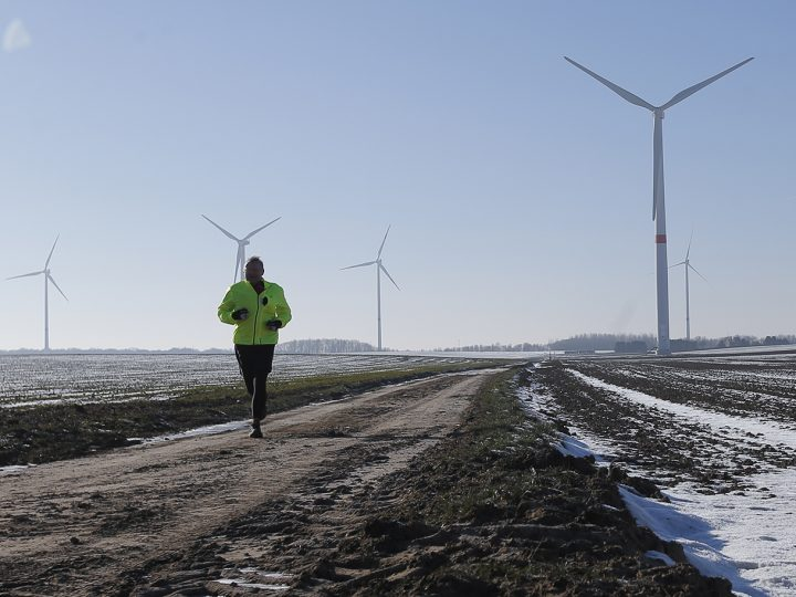 epa05731124 A man runs along a path in the frozen landscape of a wind farm near Perwez,  Belgium, 19 January 2017. Due to freezing temperature, high pressure, low winds and problems at some nuclear plants in Belgium and France, Belgium is close to activating their strategic reserves.  EPA/OLIVIER HOSLET