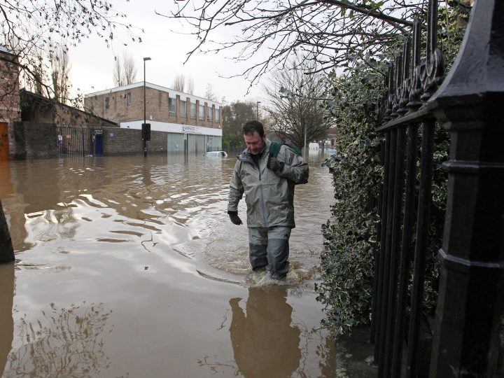 epa05082085 A local resident returns to his flooded home from fetching supplies on Park Crescent in York city centre, North Yorkshire, Britain, 28 December 2015. The nearby river Ouse burst it's banks after heavy rainfall over the UK Christmas Boxing Day public holiday, causing widespread flooding across the north of Britain with many residents being evacuated by rescue services.  EPA/LINDSEY PARNABY
