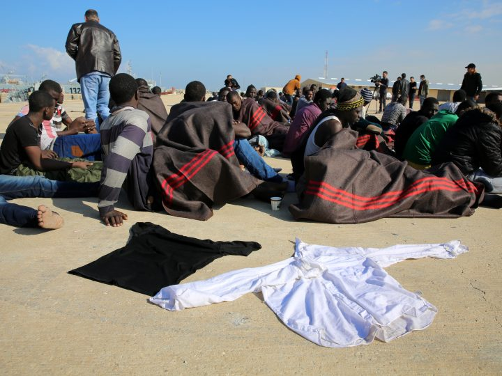 epa05078187 A group of the 108 migrants rescued by the Libyan Coast Guards rest near their clothes left to dry under the sun after their arrival at a naval base in Tripoli, Libya, 21 December 2015. According to reports, Libyan Coast Guards rescued a group of 108 migrants after their boat sank in the Mediterranean Sea near Janzur, while two bodies were recovered and 10 still missing.  EPA/STRINGER