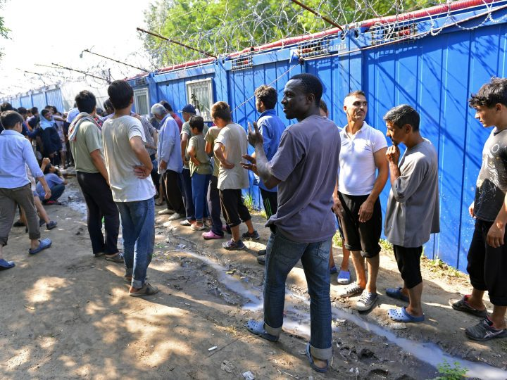 epa05440660 Migrants queue up in their camp at the border between Serbia and Hungary, in front of container buildings of a Hungarian tranzit zone at Horgos, Northern Serbia, 25 July 2016. The transit zone is a kind of border station where migrants and refugees intending to continue their journey to the European Union can apply for refugee status in Hungary.  EPA/Edvard Molnar HUNGARY OUT
