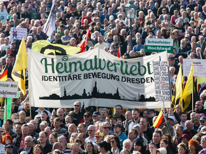 epa05587743 Supporters of the PEGIDA (Patriotic Europeans Against the Islamisation of the Occident) movement carry flags and placards as they gather on the Theatre Square in Dresden, Germany, 16 October 2016. Banner in center reads: 'Home country loving - Identity movement Dresden'. The far-right, anti-Islam PEGIDA movement celebrated its second anniversary with a rally of several thousands in Dresden.  EPA/OLIVER KILLIG