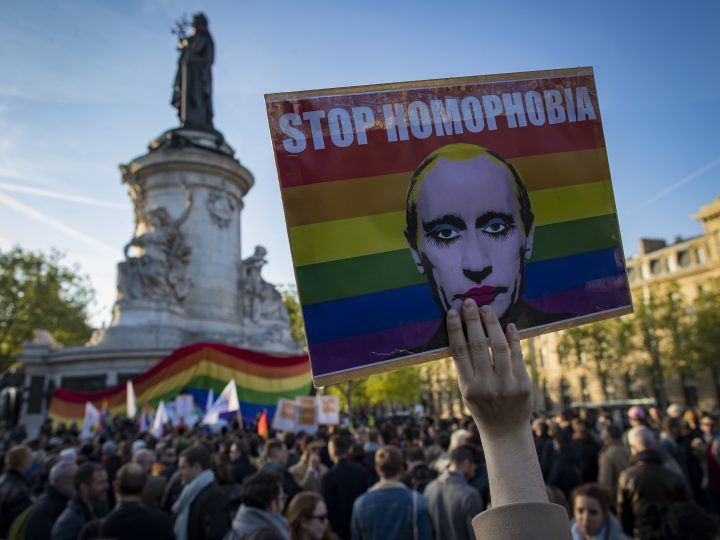epa05917734 A demonstrator holders a placard depicting Russian president Vladimir Putin with the label 'Stop Homophobia', to denounce the anti-gay campaign launched in the Russian province of Chechnya, during a protest held on Place de la Republique in Paris, France, 20 April 2017. Several  dozen men suspected of being homosexuals have been rounded up and detained by authorities in Chechnya, with at least three men allegedly killed so far.  EPA/IAN LANGSDON