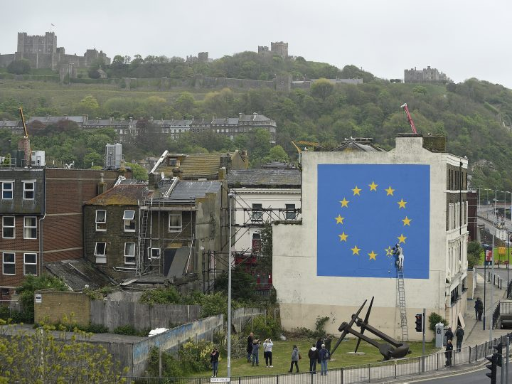 epa05950447 A view of the Brexit-inspired mural by Banksy, showing a worker chipping away at a star on a EU flag, that has been painted on the side of a building in Dover, Britain, 08 May 2017. The artwork emerged overnight under Dover Castle near the ferry terminal, which connects the UK with mainland Europe. The mural, which was confirmed by Banksy's representatives to be a genuine work by the British street artist, is his first comment on the Brexit vote last year.  EPA/GERRY PENNY