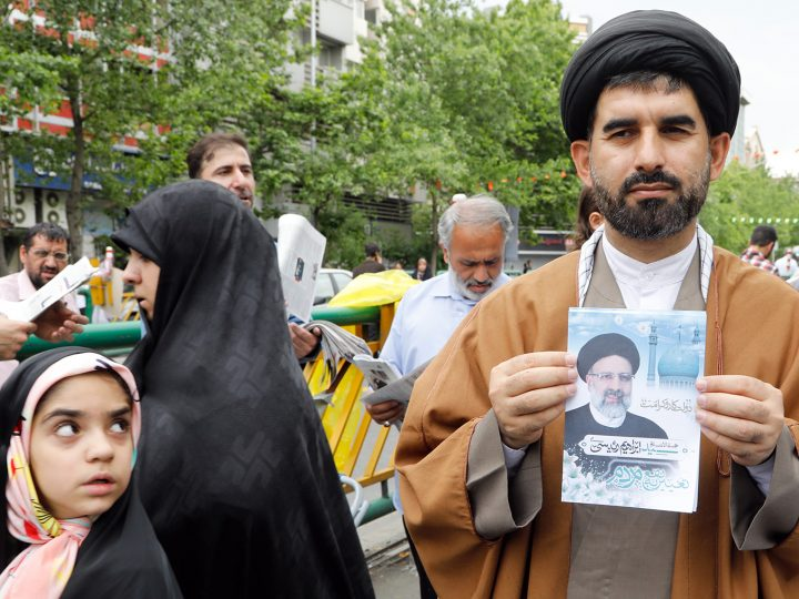 epa05959075 An Iranian cleric holds an electoral poster of Iranian presidential candidate Ebrahim Raisi  after Friday prayers in Tehran, Iran, 12 May 2017. Media reported that Raisi is the main contender against president Hassan Rouhani in the upcoming presidential elections. Iranians will go to the polls on 19 May.  EPA/ABEDIN TAHERKENAREH
