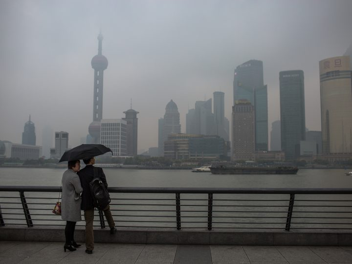 epa05892419 Chinese tourists visit the Bund with the Pudong skyline towers seen through heavy smog during a rainy and polluted day in Shanghai, China, 06 April 2017.  EPA/ROMAN PILIPEY