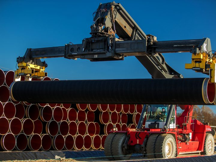 epa05662429 A special crane stacks pipes weighing several tons each which will be used for the construction of the Nord Stream gas pipeline in the Sassnitz-Mukran harbour in northeastern Germany, 06 December 2016. The first sections of the 1,200 kilometer pipeline were delivered in late October 2016. Around 2,000 of a total 90,000 steal pipe components are currently being stored on the island of Ruegen. According to the Gazprom subsidiary Nord Stream 2 AG, the assembly works will begin in mid-2017. So far the political controversial pipeline, which will have a total capacity of some 55 billion cubic meters, has not recieved building permission.  EPA/JENS BUETTNER