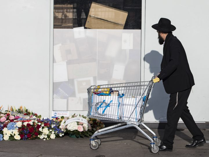 epaselect epa05699310 A man walks past wreaths layed in front of the Hypercacher market by the city of Paris to mark two-year anniversary of the attack, in Paris, France, 05 January 2016. France this week commemorates the victims of the 07 and 09 January 2015 Islamist militant attacks on satirical weekly Charlie Hebdo and a Jewish supermarket, with the offical wreath-laying ceremonies two days ahead of the actual anniversary because it falls on the Sabbath.  EPA/IAN LANGSDON