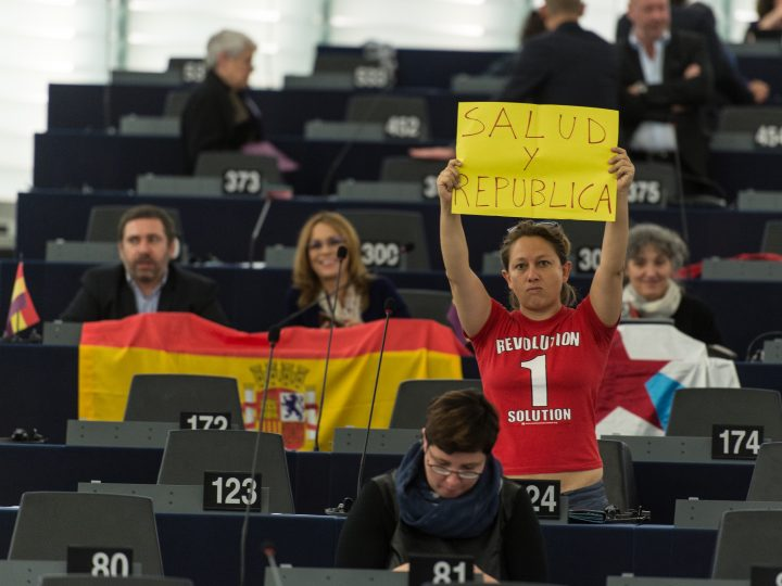 epa04966985 Eleonora Forenza from the Confederal Group of the European United Left - Nordic Green Left wears a t-shirt reading 'Revolution 1 Solution' while holding a banner 'Salud y Republica' (Health and Republic) before the speech of King Felipe of Spain in the European Parliament in Strasbourg, France, 07 October 2015.  EPA/PATRICK SEEGER