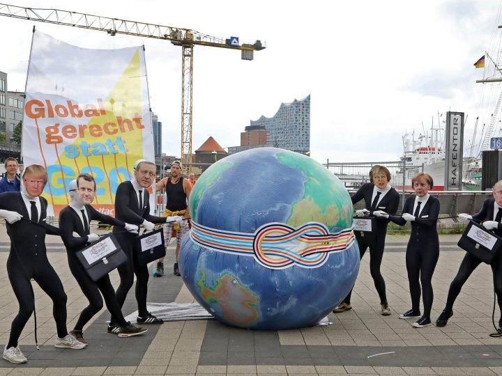 epa06064760 Activists disguised as (L-R) US President Donald Trump, French President Emmanuel Macron, Turkish President Recep Tayyip Erdogan, British Prime Minister Theresa May, German Chancellor Angela Merkel and Russian President Vladimir Putin, squeeze a big inflated rubber globe during an event organized by the activist group Attac, to protest against issues of globalisation in preparation for the upcoming G20 summit in Hamburg, northern Germany, 04 July 2017. The G20 Summit (or G-20 or Group of Twenty) is an international forum for governments from 20 major economies. The summit is taking place in Hamburg 07 to 08 July 2017.  EPA/FOCKE STRANGMANN