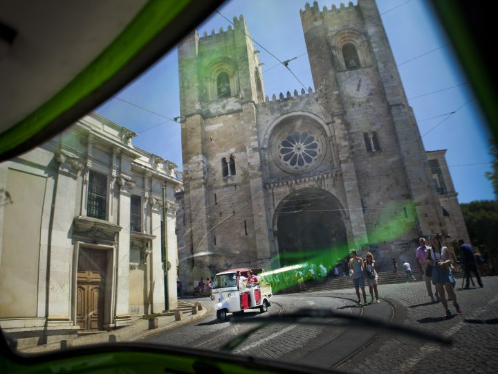 epa04346797 A picture dated 06 August 2014 shows tourists passing by The Patriarchal Cathedral of St. Mary Major or the Lisbon Cathedral as they take a ride in a Tuk Tuk, in Lisbon, Portugal. The city had received many tourism awards recently. Those visiting Lisbon have many possibilities to discover the Portuguese capital.  EPA/MARIO CRUZ