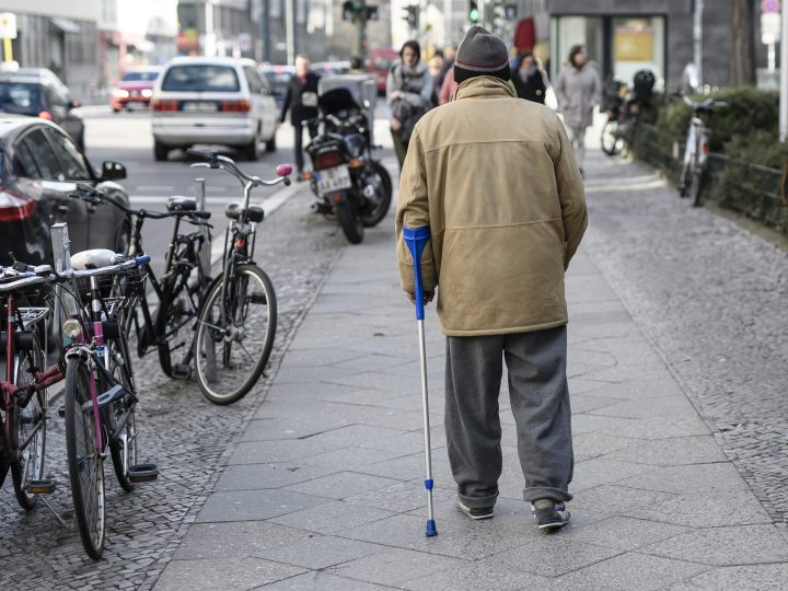 epa05820580 A beggar with a crutch walks along a street in Berlin, Germany, 28 February 2017. On Thursday, 02 March 2017, the 'Paritaetische Gesamtverband', the head organization of German Public Welfare institutions and organizations, will be presenting its poverty report 2017.  EPA/CLEMENS BILAN