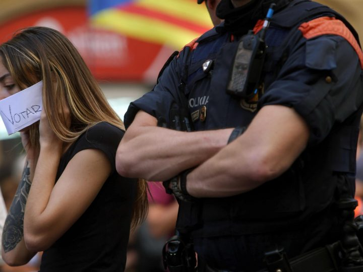 epa06215993 A woman protest next to a Catalan Police officer at the Catalan Foreign ministry regional seat in Barcelona, Catalonia, northeastern Spain, 20 September 2017. Spanish Civil Guard carried out different searches for documents related to the '1-O Referendum' resulting in the arrest of 14 people, including some Catalan Government's top officials, according to sources of the investigation. Thounsands of Catalans took the streets to protest against the police's action.  EPA-EFE/Toni Albir