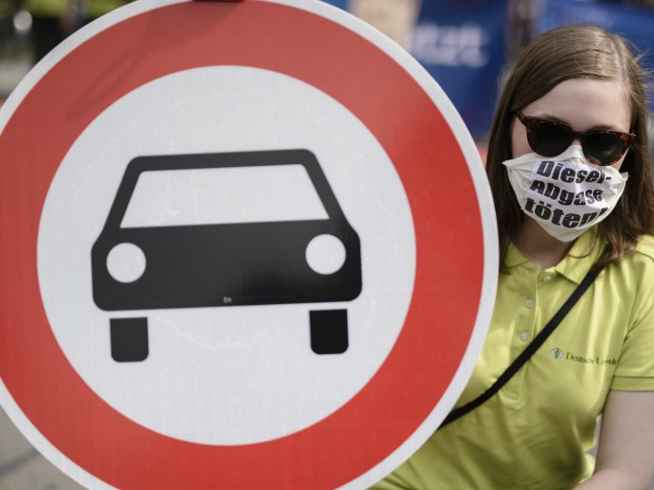epa06120954 A protestor wears a mask and a cardboard reading 'Diesel-Abgase toeten! (Diesel emission kills), and holds a traffic sign meaning, 'passage for cars forbidden' in front of the Ministry of Transport, in Berlin, Germany, 02 August 2017. Representatives of politics and German car industry meet for the so called 'Diesel Summit' on 02 August 2017 at Traffic Ministry to discuss the issue of nitrogen oxide emissions of Diesel engines built in cars of German brands.  EPA/CLEMENS BILAN
