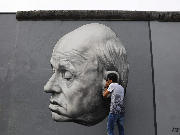 epa06154397 A tourist poses in front of a part of the artwork 'Thank You Andrej Sacharow' by Dimitri Vrubel as he visits the East Side Gallery in Berlin, Germany, 19 August 2017. The world's largest open-air gallery East Side Gallery covers a length of more than 1.3 kilometres. It features some 105 artworks painted on the east side of the former Berlin Wall at the Spree river, that seperated the city in the Cold War. The gallery was declared a national monument in November 1991.  EPA/ABIR SULTAN