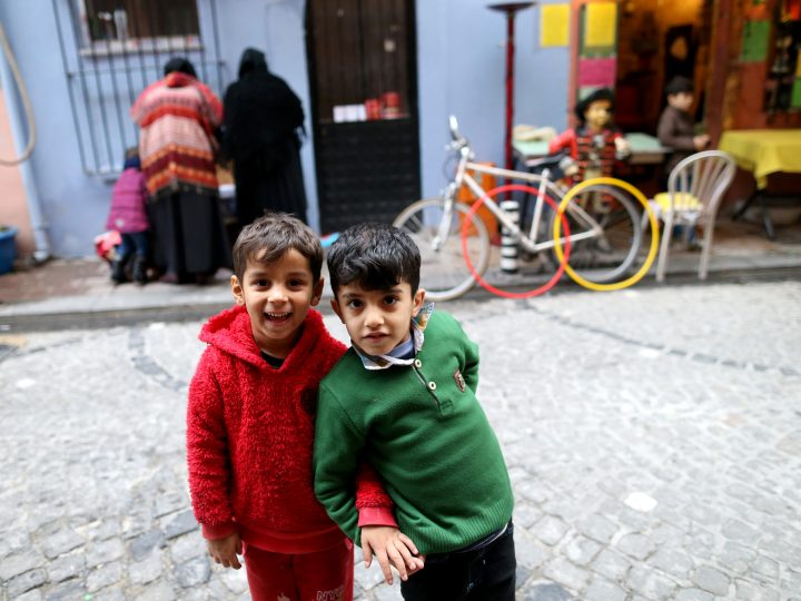 epa06344054 Syrian refugees children poses as their mothers check free clothes baskets on the street of the historical neighborhood of Balat, Istanbul, Turkey, 22 November 2017.  EPA-EFE/ERDEM SAHIN