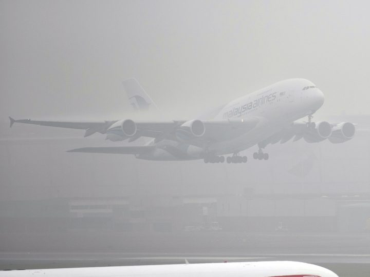 epa05744244 Planes of the British Airways airline gather on the runway as a plane of Malaysia Airlines takes off during thick fog delays departures from Terminal 5 Heathrow Airport in London, Britain, 23 January 2017. Freezing foggy weather threatens to disrupt traffic and travel plans as thick fog saw 100 flights cancelled at Heathrow.  EPA/WILL OLIVER