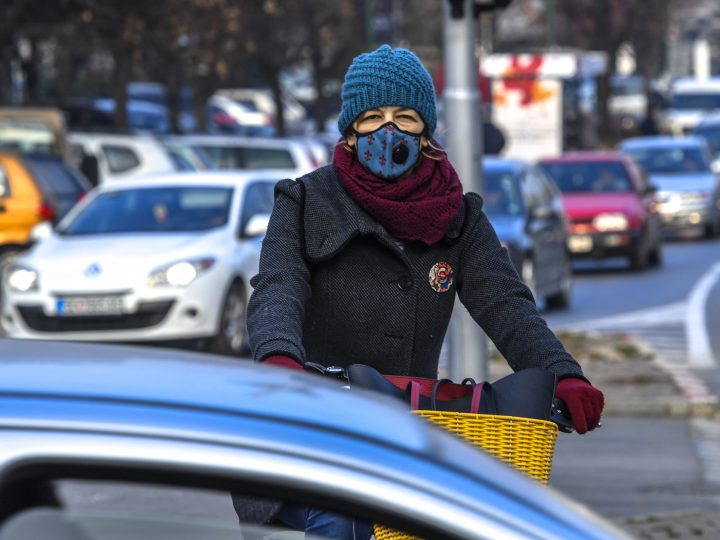 epa06407140 A woman wears a protective mask while riding her bicycle between cars in the center of Skopje, the former Yugoslav Republic of Macedonia, 27 December 2017. Macedonian government ordered free public transportation as part of emergency measures to combat air pollution.  EPA-EFE/GEORGI LICOVSKI
