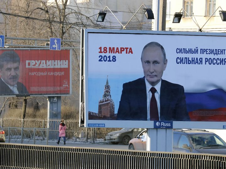 epa06443375 A woman walks past an election poster reading 'Strong President Strong Russia' in support of Russian President Vladimir Putin (R), and a self-nominated candidate in the upcoming presidential election and Presidential candidate from Russian Communist Party Pavel Grudinin (L), in St.Petersburg, Russia, 16 January 2018. Presidential election in Russia is scheduled for 18 March 2018.  EPA-EFE/ANATOLY MALTSEV
