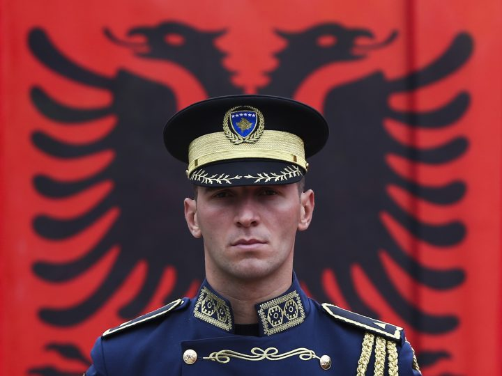 epa03484864 A member of thr Kosovo Security Forces stands guard in front of the Albanian national flag during a celebration within the frame of the anniversary of independence, in the northern town of Mitrovica, Kosovo, 24 November 2012. On 28 November 2012, Albanians will celebrate the 100th anniversary of independence from the Ottoman Empire.  EPA/VALDRIN XHEMAJ