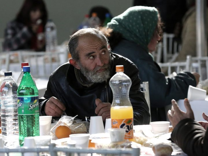 epa05694398 A Greek man eats a as people eat free meals during a New Year's Day meal for the homeless and poor that was provided by the city of Athens, in Athens, Greece, 01 January 2017. The Athens municipality's Reception and Solidarity Centre served the traditional luncheon on New Year's Day to more than 1,000 poor citizens.  EPA/SIMELA PANTZARTZI
