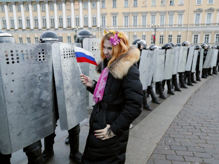 epa06481767 A supporter of opposition leader Alexei Navalny poses for photographers in front of riot police officers during an opposition non-sanctioned rally in the centre of St. Petersburg, Russia, 28 January 2018. In the absence of their candidate Alexei Navalny opposition calls to boycott president elections. Reports on 28 January 2018 state Navalny was arrested by Russian police during a opposition rally in Moscow.  EPA-EFE/ANATOLY MALTSEV