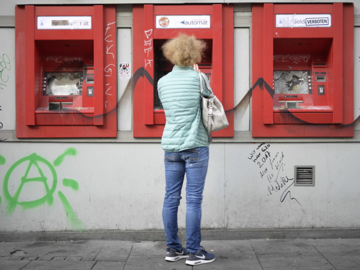 epa06074866 A woman stands infront of three destroyed ATM cash machines of a savings bank in the 'Schanzenviertel' during the G-20 summit in Hamburg, Germany, 08 July 2017. The G20 Summit (or G-20 or Group of Twenty) is an international forum for governments from 20 major economies. The summit is taking place in Hamburg 07 to 08 July 2017.  EPA/CLEMENS BILAN