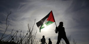 epa06575317 A Palestinian protester holds a Palestinian flag during clashes between Israeli troops and Palestinian protesters, near the border between Israel and east Gaza Strip, 02 March 2018. Palestinian demonstartors are protesting the US President decision to  recognize Jerusalem as the capital of Israel. At least 11 Palestinian protesters were reported injured during the clashes near the border east Gaza Strip.  EPA-EFE/MOHAMMED SABER