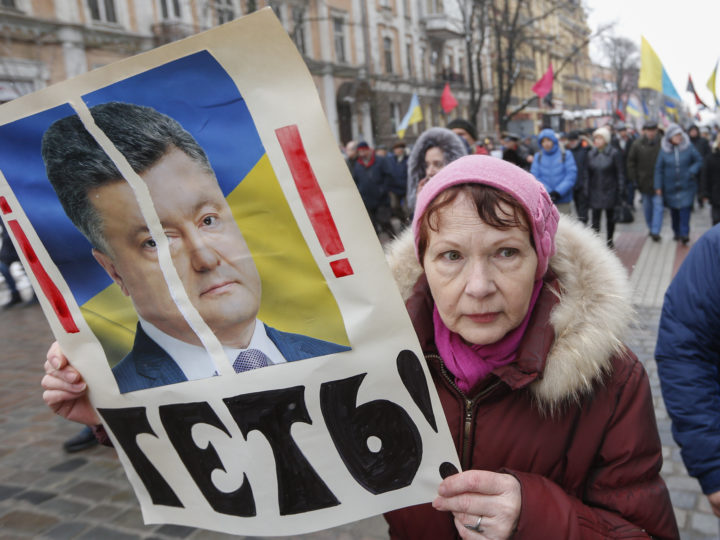 epa06539988 Protestor carries a portrait of President Poroshenko and slogan Get-out! during their rally in downtown Kiev, Ukraine, 18 February 2018. Protesters and supporters of the former Georgian president and ex-Odessa Governor Mikheil Saakashvili are demanding the Ukrainian parliament to accept a law about the impeachment of the president. Mikheil Saakashvili, ex-Georgian President and leader of the 'Movement of New Forces' Ukrainian party was detained in a Kiev and was deported to the Poland on 12 February 2018.  Public protests are held since 17 October 2017 with demands for Ukrainian lawmakers being stripped their parliamentary immunity, a modification of the electoral legislation as well as the establishment of a specialized Anti-Corruption Court.  EPA-EFE/SERGEY DOLZHENKO