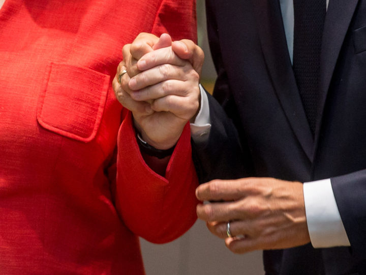 epa06849361 French President Emmanuel Macron (R) and German Chancellor Angela Merkel hold hands at the start of the second day of an European Council summit in Brussels, Belgium, 29 June 2018. EU countries' leaders meet on 28 and 29 June for a summit to discuss migration in general, the installation of asylum-seeker processing centers in northern Africa, and other security- and economy-related topics including Brexit.  EPA-EFE/STEPHANIE LECOCQ