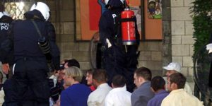 BRU22 - 20000616 - BRUSSELS, BELGIUM : English soccer fans with their hands cuffed sit on the ground and are guarded by Belgian riot police after being arrested following clashes with Turkish supporters in Brussels on Friday evening, 16 June 2000. (ELECRONIC IMAGE) EPA PHOTO EPA/MICHELE LIMINA/ML/kr