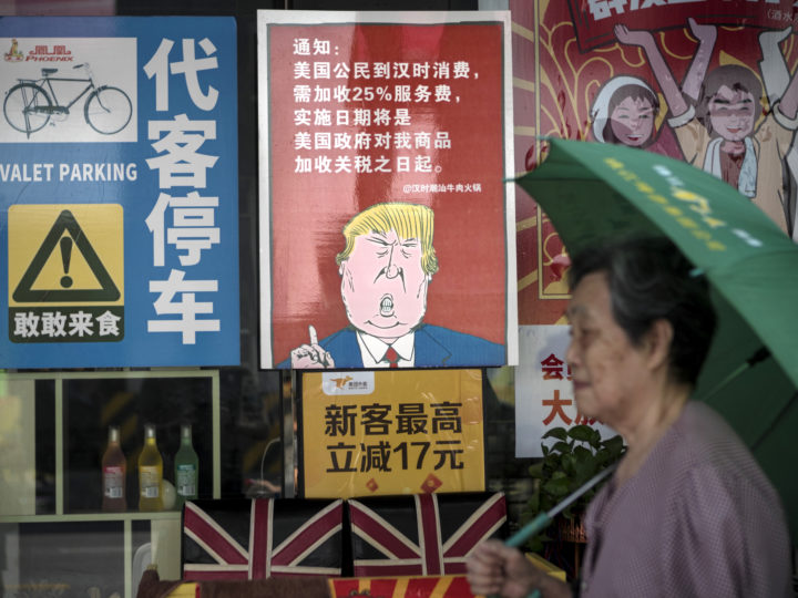 epa06947394 A woman passes by a restaurant with a poster depicting US President Donald J. Trump, stating that all US costumers will be charged 25 percent more than other customers starting from the day president Trump started the trade war with China, in Guangzhou, Guangdong Province, China, 13 August 2018. US President J. Trump announced on 10 July that US is preparing to impose 10 percent tariffs worth 200 billion US dollars on imported goods from China. These tariffs would affected mainly consumer goods.  EPA-EFE/ALEKSANDAR PLAVEVSKI