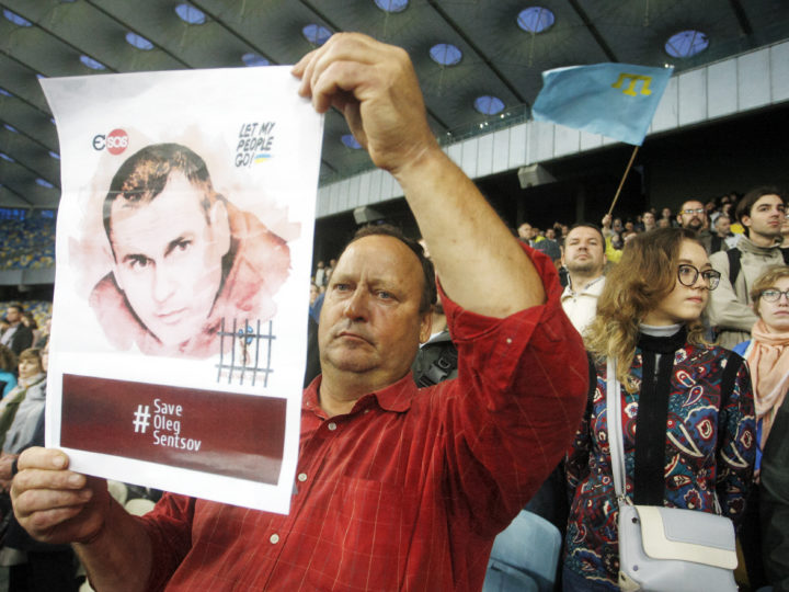 epa06859596 An Ukrainian man holds a poster with an image of Ukrainian film director Oleg Sentsov,during a flash mob in support of Sentsov, at the NSC Olimpiyskiy stadium in Kiev, Ukraine, 02 July 2018. Oleg Sentsov was arrested in Crimea on 11 May 2014 by Russian Federal Security Service and accused of organizing terrorist acts in Crimea. Sentsov denies all accusations and considers his case as politically motivated.  EPA-EFE/STEPAN FRANKO