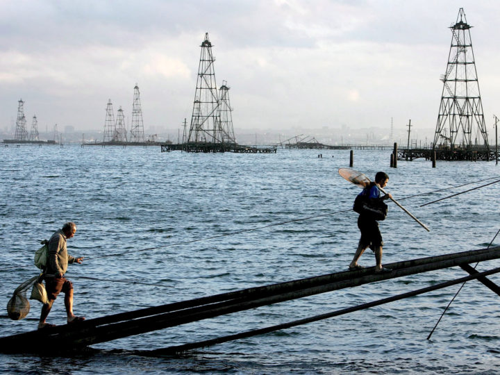 epa06945531 (FILE) - Two sailors walk in front of the oil derricks on the Caspian Sea near Baku, Azerbaijan, 07 October 2005 (reissued 12 August 2018). The leaders of five countries bordering the Caspian Sea - Caspian Five Russia, Iran, Kazakhstan, Azerbaijan and Turkmenistan - plan tosign the Convention of the legal status of the Caspian Sea at the Aktau summit on 12 August. It is expected to clarify the resources-rich Caspian Sea's status of whether being a lake or a sea, and ban non-littoral states from mliitary presence in the world's largest enclosed inland body of water.  EPA-EFE/SERGEI ILNITSKY