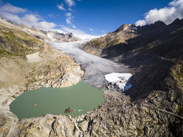 epa07017579 A lake of molten ice from the Rhone Glacier is pictured prior to a visit of the micro organism sample collection site of the Center for Changing Alpine and Polar Environments of the Ecole Polytechnique Federale de Lausanne (EPFL) in Obergoms, Switzerland, 13 September 2018. By collecting and analyzing micro organisms from some of the world's biggest glacier-fed streams in the upcoming years, the team of EPFL scientists aims to understand how the microbial life has adapted to extreme environments, additionally allowing to unravel some of the implications of vanishing glaciers as a result of climate change.  EPA-EFE/VALENTIN FLAURAUD PICTURE TAKEN WITH A DRONE