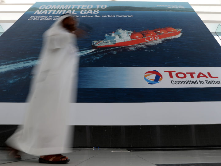 epa07162758 A Gulf visitors walks in front of a big poster for Total company at Abu Dhabi International Petroleum Exhibition and Conference (ADIPEC) in Abu Dhabi, United Arab Emirates, 13 November 2018. ADIPEC, a meeting place of the international oil and gas community, runs between 12 and 15 November 2018.  EPA-EFE/ALI HAIDER